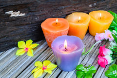 Candles and flowers plastic beautiful. On bamboo table on old wood background Royalty Free Stock Image