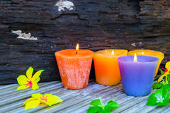Candles and flowers plastic beautiful. On bamboo table on old wood background Royalty Free Stock Images