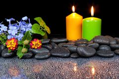 Candles, flowers and spa stones on black background . Candles, flowers and spa stones on black background stock photo