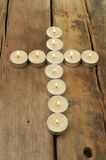 Candles form a cross on wood Royalty Free Stock Image