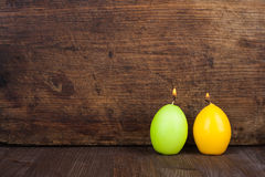 Easter memories. Candles in the form of eggs on the background of a wooden surface Royalty Free Stock Photos