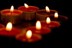 Candles forming heart. Close up of candles lit only by them selves stock photography