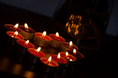 Candles forming heart. Only lit by thmselves on dark background royalty free stock photography