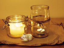 Candles in glass burning romantic celecration concept wooden kitchen Royalty Free Stock Images