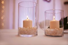 Candles on a glass candlestick. Burning candle in a round glass candlestick with decorative seashells. Burning candle in a round glass candlestick with stock image