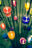 Candles in glasses. Colorful candles in glasses with flower style stand (Focused on Red and Blue Stock Images