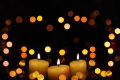 Candles glowing with defocused lights. stock photos