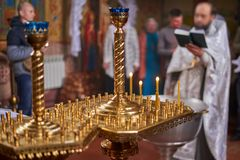 Candles in a golden chandelier in the Orthodox Church, close-up, priest with parishioners in the background out of focus. Candles in a large golden chandelier in stock image