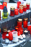 Candles on grave. Various grave candles on a snowy tomb Royalty Free Stock Photo
