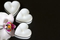 Candles hearts with orchid on black background love Royalty Free Stock Images