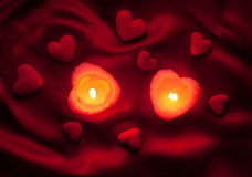 Candles and hearts on red silk Stock Images