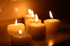 Candles. Holiday candles burning on a white background and reflected Royalty Free Stock Photo