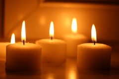 Candles. Holiday candles burning on a white background and reflected Royalty Free Stock Image