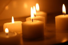 Candles. Holiday candles burning on a white background and reflected Royalty Free Stock Images