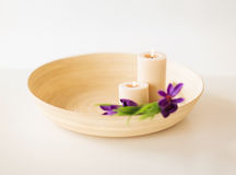 Candles and iris flowers in wooden bowel Royalty Free Stock Photography