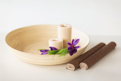 Candles and iris flowers in wooden bowel and mat Royalty Free Stock Photography