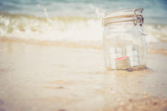 Candles in jar with beautiful beach. And sea in background, vintage style Stock Photos