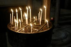 Candles in Kettle, Jerusalem. Candles burning in a kettle by the Mourning Place of Mary in the Church of the Holy Sepulchre, Jerusalem Royalty Free Stock Photo