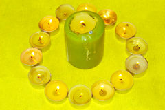 Candles. Large and small candles burning on the table Royalty Free Stock Photo