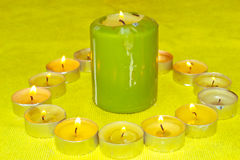 Candles. Large and small candles burning on the table stock image