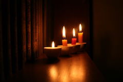 Candles in a library. Four candles with antique books in romantic light royalty free stock photography