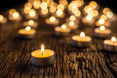 Candles light in advent. Christmas candles burning at night. Golden light of candle flame Stock Photos