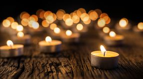 Candles light in advent. Christmas candles burning at night. Golden light of candle flame.  Stock Photo