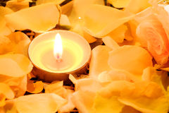 Candles light on beautiful fresh yellow rose petals with water d Royalty Free Stock Photo