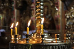 Candles light on chandelier in ancient Orthodox church Royalty Free Stock Photos