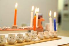 Candles light in Hanukkah menorah stock images