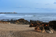 Candles and lighthouse on the coast Royalty Free Stock Photography