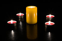 Candles are lighting on the table, dark background. A large candle surrounded by small candles on a dark background in the light of the flame Royalty Free Stock Image