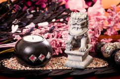 Candles and lion sculpture with pink flowers spa Stock Images