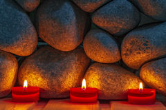 Candles are lit on the background of the  stones. Stock Images