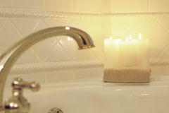 Candles lit in a blurred romantic bath. A blurred background of relaxing candles and a warm spa bath Stock Image