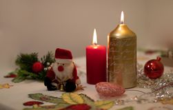 Candles lit with Christmas decoration and a Santa Claus doll on a tablecloth. Colored candles lit with Christmas decoration and a Santa Claus doll on a royalty free stock photos