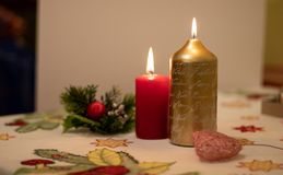 Candles lit with Christmas decoration on a tablecloth. Candles of different colors with Christmas decoration on a tablecloth stock photos