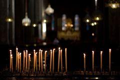 Candles lit in church. Candles lit in a dark church , chandeliers and stained glass windows in background Stock Photos