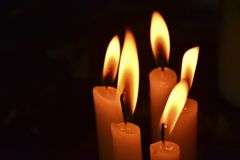 Candles lit in the dark. With space to write some text on the left of the image, there are 5 candles in total stock photo