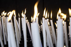 Candles lit lourdes. Candles lit in chapel of Lourdes, religious symbols and terrorism Royalty Free Stock Image