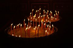 Candles lit in a stand with sand in a church in Prague royalty free stock photo