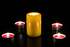 Candles are lit on the table, dark background. A large candle surrounded by small candles on a dark background in the light of the flame Stock Photo