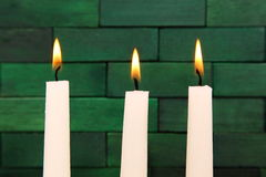 Candles. Lit up candles against the wooden green background Royalty Free Stock Photo