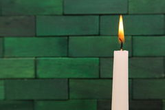 Candles. Lit up candles against the wooden green background Royalty Free Stock Photography