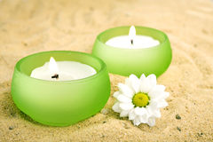 Candles and little daisy flower on sand Royalty Free Stock Photography