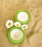 Candles and little daisy flowers on sand Royalty Free Stock Photography