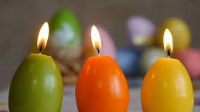 Candles made in shape of easter egg. Burning candles. Green, orange, yellow. Easter eggs candles and colorful Easter stock video footage