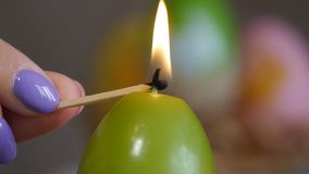 Candles made in shape of easter egg. Green candles. Female hand lights candles. stock video