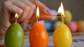 Candles made in shape of easter egg. Green, orange, yellow. Female hand lights candles. stock video footage