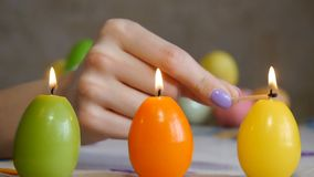 Candles made in shape of easter egg. Green, orange, yellow. Female hand lights yellow candles. Two candles are burning stock video footage